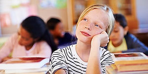 APS-ADHD-children-girl-daydreaming-in-cl