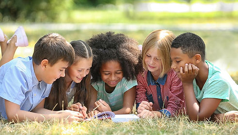 Young-Kids-Reading-Book-on-Grass-Outside