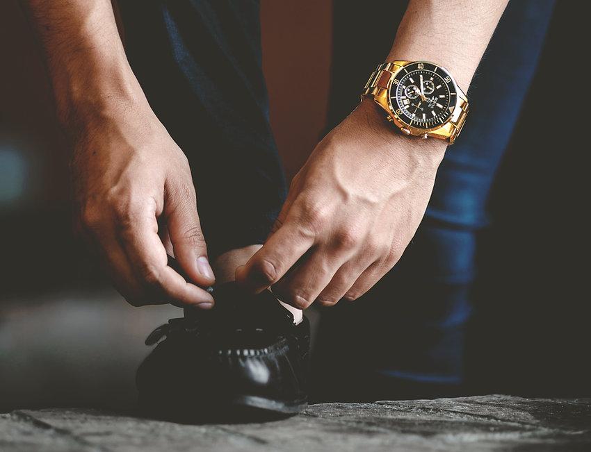Mann mit Uhr seine Schuhe binden