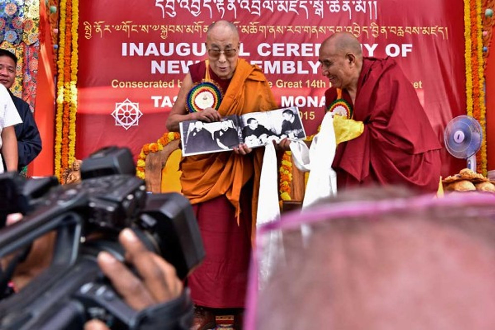 Khen Rinpoche Kachen Lobzang Tsetan, Abbot of the Tashi Lhunpo Monastery presenting a gift to His Holiness the 14th Dalai Lama at inaugration of Monastery New Assembly Hall