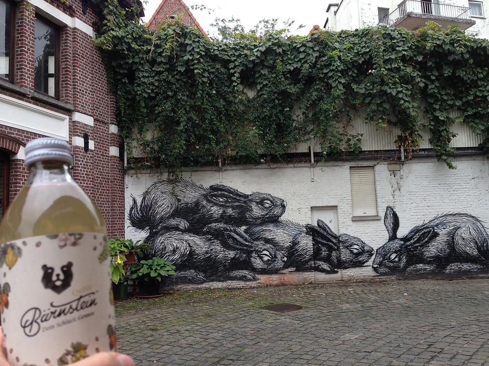 Bärnstein Quitte vor dem Hasen-Motiv des Streetartkünstlers ROA in Gent, Belgien.