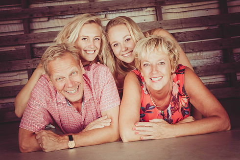 Stapelen! Papa en mama onderop, hun dochters er bovenop! Tijdens een gezinsfotoshoot worden jullie in diverse poses gefotografeerd door deze portretfotograaf.  Family portrait. Father, Mother and two daughters.