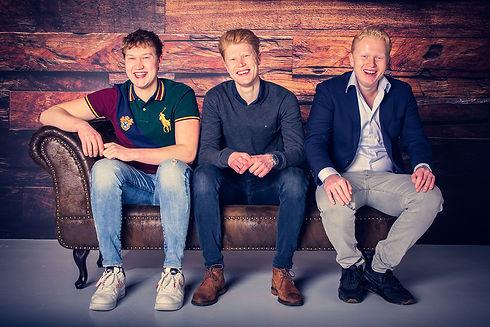Deze drie broers hebben een professionele portretfoto laten maken door bekende fotografe Nikki Hoff in haar moderne fotostudio Studio86. De broers zitten op een bruine chesterfield bank voor een houten wand. Wil jij de prijslijst van een fotoshoot bekijken? Ga dan naar www.studio86.nl/prijzen