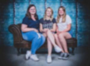 Tijdens deze fotoshoot zitten de zussen op een stoere chesterfield bank voor een industriële achtergrond. Deze portret foto is gemaakt tijdens een zussen fotoshoot. Photoshoot of 3 sisters made in the photo studio.