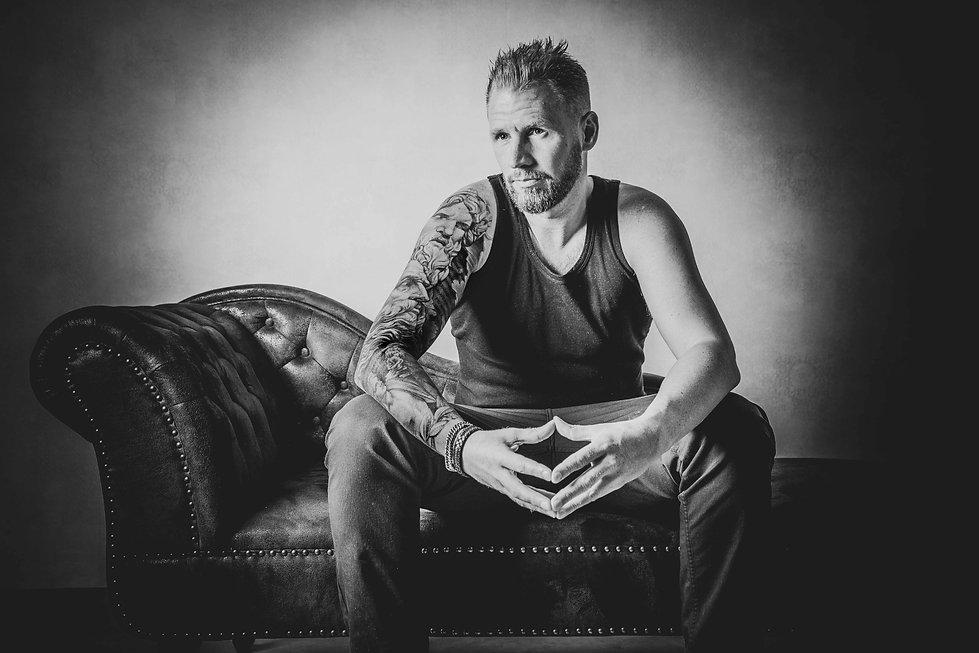 Zwart wit foto van een man met een sleeve die op een bank zit. Wil jij ook een tattoo fotoshoot boeken? Deze fotograaf is gespecialiseerd in het vastleggen van tattoo's op een toffe manier. Black and white photo of a man with a sleeve sitting on a couch. Wanna book a tattoo photoshoot? This photographer is specialised in tattoo photography.