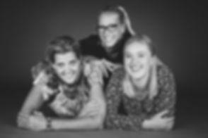 Zwart wit foto van een moeder dochter fotoshoot. Hier liggen moeder en dochter op de grond, het kleine zusje ligt bovenop haar zus en moeder. Een professionele portretfoto gemaakt bij de beste fotograaf van Nederland. Black and white picture of a daughter mother photo shoot. Professional portrait photography.