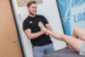 Hier zie je een fysiotherapeut/ manueel therapeut die aan het werk is in zijn praktijk. Dit sfeerbeeld is gemaakt door interieur fotograaf Nikki Hoff. Physio therapist in action. Business photoshoot.