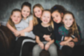 In de fotostudio zijn er diverse achtergronden en accessoires. Hier zitten de meiden op een bruine chesterfield bank en worden ze geknuffeld door hun vriendinnen. Deze kindershoot is tijdens een partijtje gemaakt.  Photoshoot with friends! Good idea for a birthday party of your daughter.