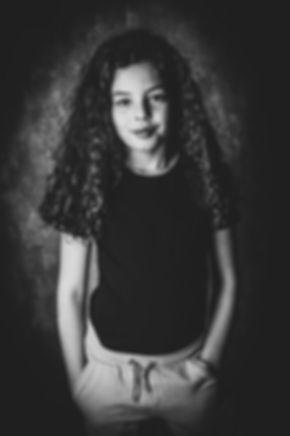 Kijk deze stoere meid eens staan! Doordat de portretfoto zwart wit is bewerkt, komt de sfeer van de foto nog beter over! Deze foto is gemaakt door de kinderfotograaf van Studio86.  Black and white photography of a young girl.