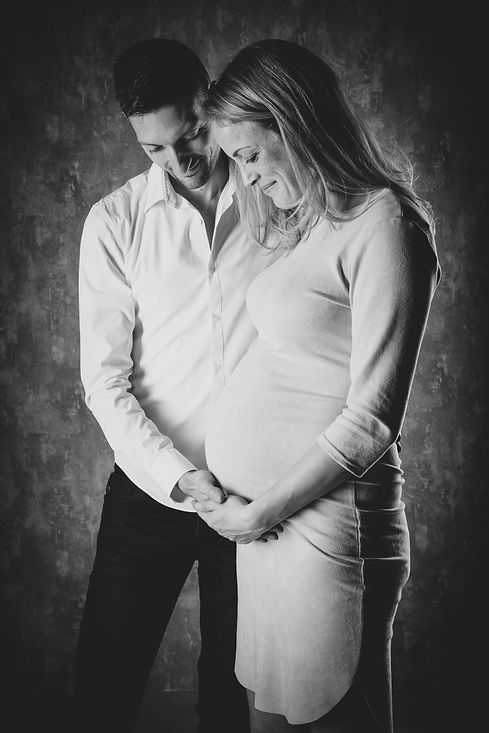 Zwart wit foto van een zwangere dame en haar man. Beide kijken ze naar beneden toe, naar de buik. Deze dame is hier 34 weken zwanger.  Black and white photo of a pregnant couple. Mommy and daddy to be. She is 34 weeks pregnant in this photo.