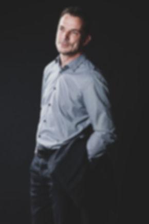 Deze sexy man op de trap is een beginnend model en heeft deze professionele fotoshoot geboekt om zijn portfolio uit te breiden. Sexy man with a jacket over hes arm.