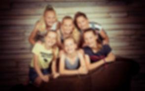 Deze 6 meiden zitten gezellig dicht bij elkaar op een bruine Chesterfield bank. Deze matcht goed met de houten achtergrond. Een gezellig kinderpartijtje vier je bij Studio86!  Photoshoot with friends!