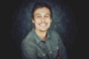 Fotograaf gezocht in Zuid Holland? Fotografe Nikki Hoff helpt jou graag bij het maken van een mooie portretfoto. Nikki is gespecialiseerd in portretfotografie en doet dit voornamelijk in haar ruim opgezette fotostudio.  Black and white photo of a handsome young man. Smiling guy.