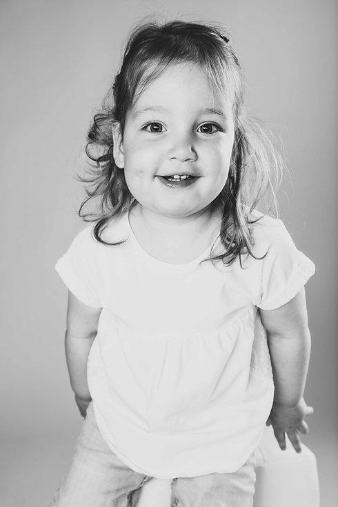 Zwart wit portretfoto van een peuter gemaakt tijdens een kinder shoot. Nikki is kinderfotograaf en heeft veel ervaring met kinderfotografie.  Black and white portrait of a young little cute girl. Toddler photography.