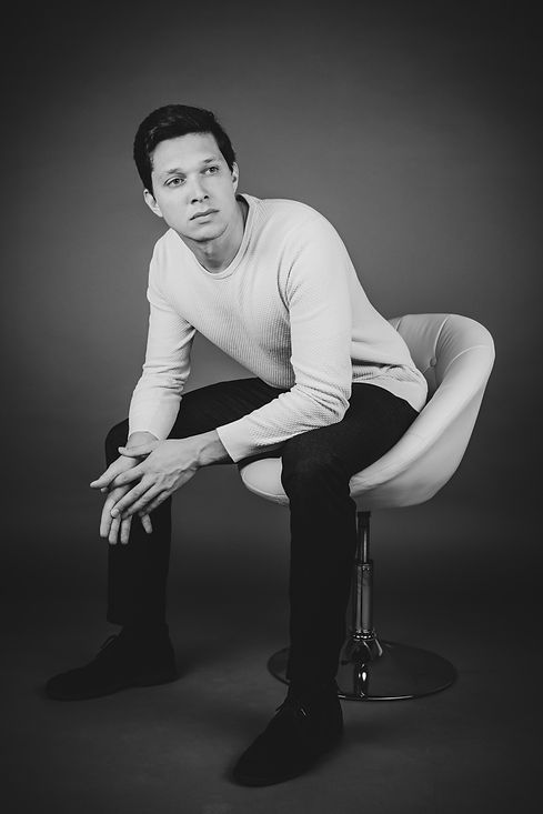 De fotostudio beschikt over divers meubilair zoals deze witte stoel. Dit is een stoere mannen foto geworden die later bewerkt is naar zwart/wit om hem extra stoer te maken.  Sexy young man sits on a white chair. Photo made during a men's photo shoot.