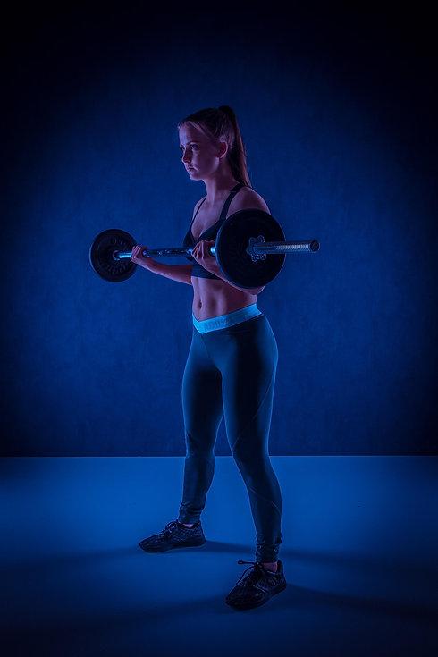 Deze afgetrainde dame doet haar oefeningen met de barbell (halterstang) terwijl professionele fitnessfotograaf haar fotografeert. Deze sportieve foto is tijdens een fitness fotoshoot gemaakt in een fotostudio. Nikki is één van de bekendste fotografen van Nederland en maakt graag professionele sportfoto's.