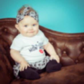 Prachtige kleine meid zit op een Chesterfield bank en er is gebruik gemaakt van een blauwe achtergrond. In deze fotostudio zijn meerdere kleuren settings en props aanwezig om een hele vrolijke kindershoot te kunnen maken!  Cute little baby photographed by a professional photographer. She is sitting on a couch in front of a blue background.