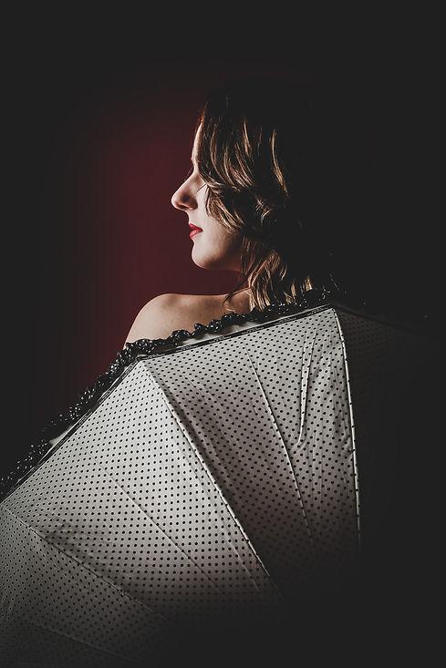 Model achter een paraplu waardoor het lijkt alsof ze naakt is, maar eigenlijk heeft ze gewoon haar kleding nog aan. Voor stijlvolle boudoir fotografie kan je terecht bij deze fotografe.  Sensual photography. Young woman hiding behind umbrella.