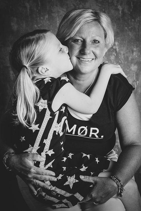 Lijkt het jou ook gaaf om een moeder/dochter fotoshoot te doen? Fotografe Nikki helpt graag bij het maken van mooie portretfoto's van jullie samen. Deze foto is in de fotostudio gemaakt en later met een zwart/wit filter bewerkt.  Mother daughter photoshoot. Daughter gives a kiss on her mothers cheek.