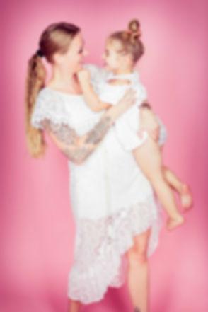 Spontane fotoshoot boeken? Dit is een ontzettend spontane, liefdevolle foto van een moeder met haar dochter. Deze vrolijke foto is gemaakt op een roze achtergrond en mama en haar kind van 2 jaar hebben allebei een witte jurk aan. Spontaneous photograph of mother and daughter. They are wearing a white dress witch looks good on this pink background.