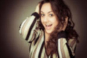 Grappige, spontane foto van een knappe vrouw. Deze close up portret foto is gemaakt in een fotostudio waarbij er gebruik is gemaakt van een reflectiescherm. Deze dame heeft haar handen in het haar en heeft een spontane uitstraling. Fun, spontaneous photo os a pretty lady. This close up portrait photo is made in the photo studio where the photographer used a reflection screen. She had her hands in her hair and a funny expression in her face.