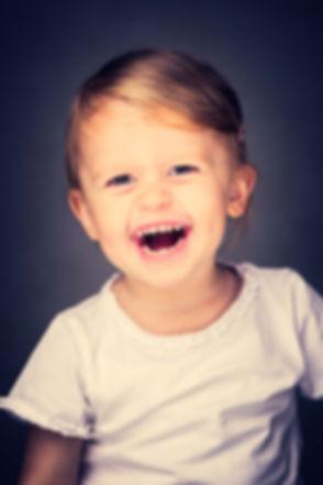 Lachend meisje gefotografeerd door bekende fotografe Nikki Hoff in haar fotostudio.  Studio photo of a young girl made by a professional photographer.