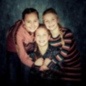 Deze zussenfoto is gemaakt tijdens een kindershoot door een bekende kinderfotograaf. Deze 3 zusjes geven elkaar een knuffel en als je goed kijkt, zie je dat ze samen een hartje vormen. Deze professionele portretfoto is gemaakt in de fotostudio van bekende fotografe Nikki Hoff.