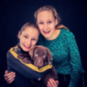 Voor een professionele fotoshoot van hond met baas ga je naar www.studio86.nl/dieren. Nikki is een goede dierenfotograaf en maakt graag een mooie fotoreportage van jouw hond of ander huisdier. Hier word de bruine labrador puppy geknuffeld door zijn twee baasjes.