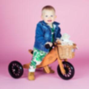 Deze peuter is jarig en is vandaag 1 jaar geworden! Zij heeft een mooie fiets kado gekregen van papa en mama die natuurlijk mee mocht naar de fotoshoot. Een vrolijke foto door de mooie lach en de roze achtergrond.  Smiling toddler on her bike. Professional kids photo made with a pink background.