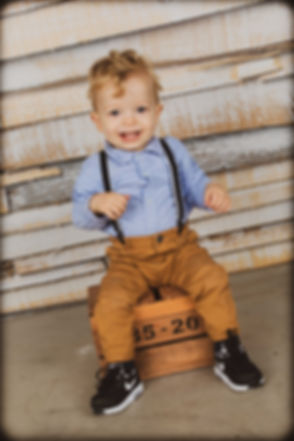 Kleuter gefotografeerd tegen een houten achtergrond. Kinderfotograaf in Alphen aan den Rijn.  Professional kids photographer made this studio photo of this toddler.