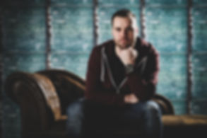Jonge man zit op een bruine chesterfield bank. Deze professionele foto is gemaakt in een fotostudio waar een industriële achtergrond aanwezig is.  Young man sits on a brown chesterfield couch. This professional photograph is taken in a photostudio.