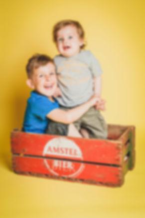 Nikki is kinderfotograaf en maakt ook graag van jouw kinderen stoere portretfoto's. Bij deze foto is er gebruik gemaakt van een zwarte achtergrond.  Portrait photo of 2 brothers in a vintage Amstel crate.