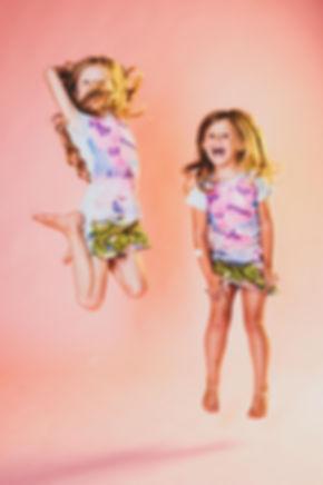 Stoere zussenshoot gemaakt door een professionele fotograaf in Alphen aan den Rijn, Zuid Holland.  Sisters jumping during a professional photoshoot.
