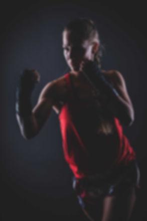 Deze dame zit op kick boxen en maakt voor deze sportfoto een move die ze heeft geleerd tijdens haar lessen. Een stoere portretfoto van een knappe vrouw gemaakt tijdens een fitness fotoshoot.  Kick box portrait photo of a young sexy woman. Made in the photostudio using a black background. Sporty photography.