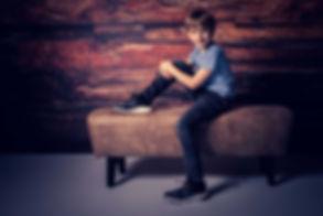 Kijk deze stoere jongen van 10 jaar eens zitten op deze lederen hocker. De fotostudio die deze stoere foto heeft gemaakt beschikt over diverse settings waaronder deze houten setting. Door één flitslamp te gebruiken word er een stoer effect gecreëerd in de foto.