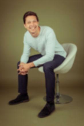 Ook King Westinga komt voor zijn casting portfolio naar Studio86 te Alphen aan den Rijn toe. Met deze olijfgroene achtergrond zijn King zijn ogen nog sprekender!  A guy on a chair. Photo for casting.
