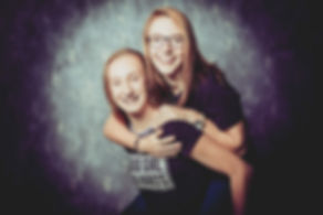 Spontane portretfoto van 2 zusjes die bij elkaar op de rug springen. Deze foto is gemaakt in de fotostudio van fotografe Nikki.  Professional portrait of two sisters. Made in a photo studio.