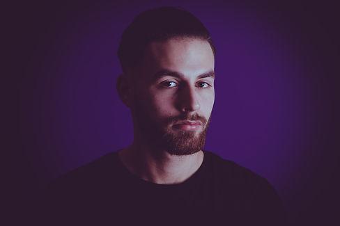 Voor een gevarieerde fotoshoot kan je het beste naar Studio86 in Zuid Holland. Door de vele settings heb jij gelijk een hele variatie aan portretfoto's die je eventueel in jouw portfolio kunt gebruiken.  Young guy photographed in a photostudio against a purple background.