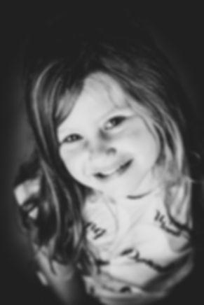 Toffe portretfoto van kind, waarbij gebruik is gemaakt van een zwarte achtergrond. Gemaakt in de fotostudio van bekende fotografe Nikki Hoff.  Black and white profile picture of a young girl.