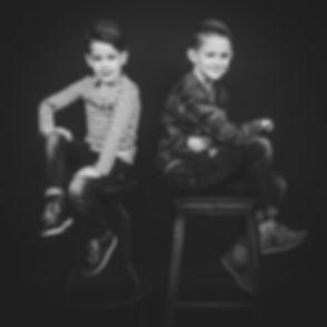 Een stoere zwart wit portret foto van 2 stoere jongens. Deze foto is gemaakt tijdens een kinderfotoshoot bij Studio86 in Alphen aan den Rijn.  Cool black and white photo of 2 young brothers. Kids photography.