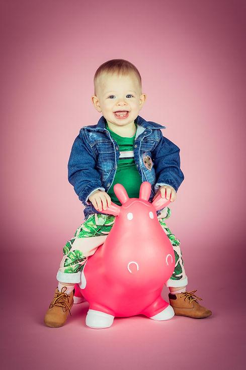 Deze peuter is 1 jaar geworden en vierde dat met een fotoshoot in de studio! Een vrolijke portretfoto door de roze achtergrond en de roze Skippy Koe.  Happy toddler smiling and sitting on a pink cow. Playful photograph.