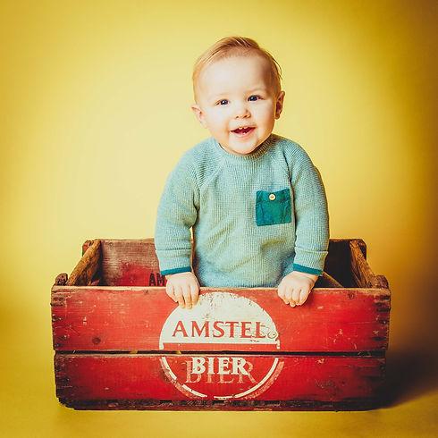Professionele portretfoto van een peuter van 1 jaar die in een Amstel kratje zit. Studio foto waarbij gebruik is gemaakt van een gele achtergrond.  Professional portrait photo of a toddler of one year old sitting in a vintage Amstel crate.