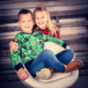 Stoere maar gezellige studiofoto van een broer en zus. Gemaakt tijdens een kindershoot in bekendste studio van Nederland. Deze fotostudio is gespecialiseerd in kinderfotografie en alle andere portretfotografie. Cool but fun photograph of a brother and sister.