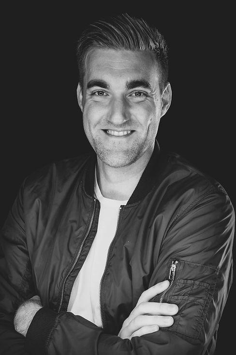 Wil jij ook een stoere portretfoto laten maken? Nikki is een professionele fotograaf en is gevestigd in Alphen aan den Rijn op de Antonie van Leeuwenhoekweg. De fotostudio staat geheel tot jouw beschikking tijdens de shoot.  Headshot of a smiling guy. Black and white portrait photography.