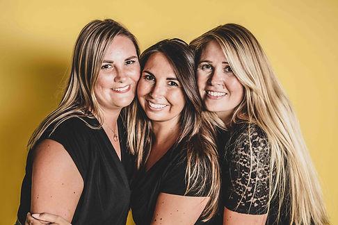 Deze vrolijke zussenfoto is met een zomerse achtergrond gemaakt tijdens een zussenshoot.  Professional portrait photo of 3 sisters.