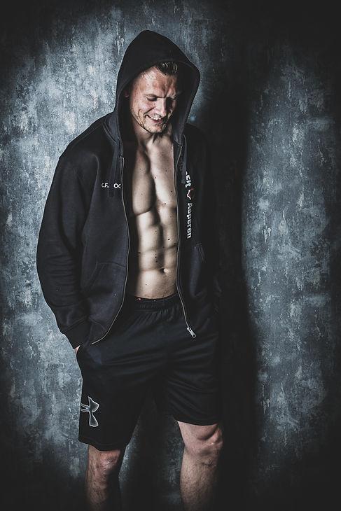 Deze knappe man heeft een hoody aan van zijn sportschool. De foto is gemaakt tijdens een fitness fotoshoot door bekende fotograaf Nikki Hoff, die eigenaresse is van een goedlopende fotostudio te alphen aan den rijn.  Handsome, smiling man wearing a hoody. You can see he's abs really well in this shot. Made in a photostudio.
