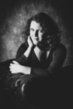 Dit zwart wit portret van deze mooie dame is gemaakt met flitslampen in de studio van een bekende fotografe. Een creatieve portretfoto doordat er creatief met het licht is omgegaan.  Black and white photo of a young woman sitting on a couch.