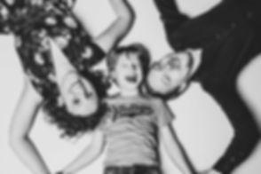 Deze zwart wit portretfoto is gemaakt door een bekende portretfotografe in haar fotostudio. Hier liggen papa, mama en hun zoon op de grond en de foto is van bovenaf genomen. Wil jij ook spontane portretfoto's laten maken van jouw gezin? Neem dan contact op met de fotostudio Studio86.