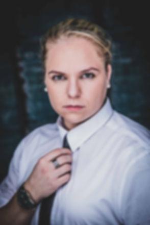 Hier zie je een stoere dame die een wit overhemd aan heeft en een zwarte stropdas draagt. Ze kijkt intens de camera in. Deze foto is gemaakt tijdens een glamour fotoshoot. Wil jij ook zo'n glamour fotoshoot boeken? Dan is deze fotografe degene die graag een profielfoto van jou zou willen maken. Tough lady with intens eyes. She's wearing a white shirt with a black tie.