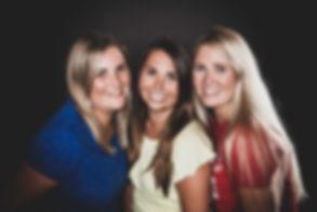 Deze zussenfoto is gemaakt met een zwarte achtergrond, zodat de gezichten en de vrolijke kleuren van de shirtjes mooi naar voren komen.  Professional portrait photo of 3 sisters.